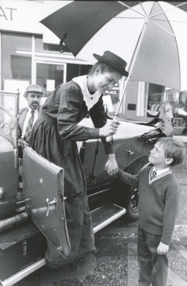 1993: Welcome Marie Curie: The historical character steps out of a 1926 Singer car to a welcome by Seaton P1 pupil Ryan Murray.