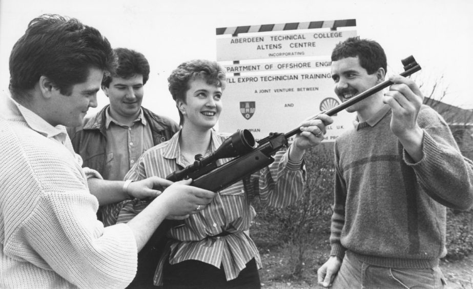 "Shell 1988-04-25 Karen Falconer (C)AJL  25 April 1988  ""Shooting Stars...Getting to grips with an air rifle at the Superstars competition held in aid of the Give a Child a Chance Appeal is Karen Falconer, aided by, from left, Evander McRae, Colin Paterson and Adrian Austin. Taking part in the competition, which runs until Thursday, are 150 trainees and 30 staff at the Shell Training Centre, Altens. There are 12 events, including swimming, running and shooting.""  Used: P&J 26/04/1988"
