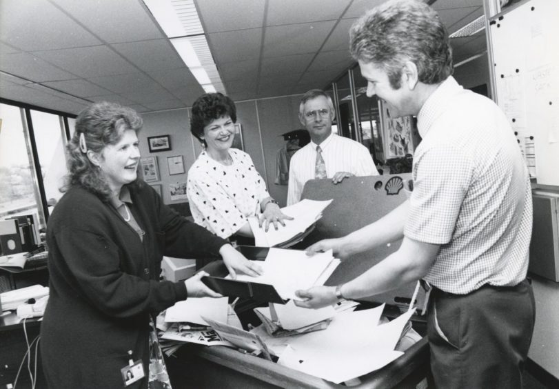 "Shell 1991-05-31 Gordon Wood (C)AJL  31 May 1991  ""Green Man: Gordon Wood (right), collects office papers for recycling in the community relations office, at Shell's Altens headquarters, from community relations officer Judith Munro (left), and visits and events officer Margaretha Simpson. Looking on is Johan Kwant.""  Used: EE 18/06/1991"