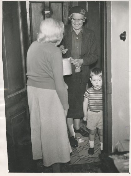 1961: A warm smile and a hot meal for Mrs G. Erskine, when Mrs B. Crawley of the WRVS calls at the door. Also pictured is Stephen Gibb (3), a neighbour of Mrs Erskine's.