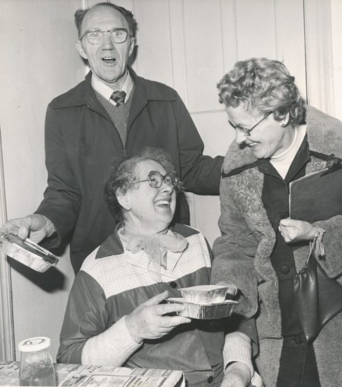 1981: Mrs Isabella Brown, Aberdeen (seated), receives her meals on wheels from Mrs Helena Rattray and her husband Francis, Gilcomstoun Land, Aberdeen.
