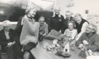 1981: Looking at one of the cardigans knitted at the Women's Royal Voluntary Services Friday (Disabled) Club, shown by deputy regional organiser Miss Ray Skinner, are some of the members and helpers at the weekly meeting.