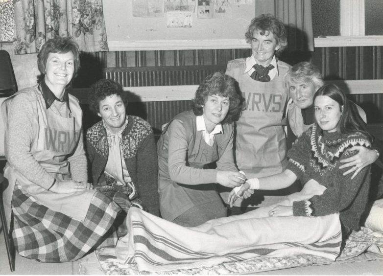 """1982: Ellon WRVS rehearse emergency first-aid during an excuse yesterday which simulated a dangerous chemicals spillage in the town. Giving treatment to """"injured"""" patient Mrs Kate Ferries is Mrs Eunice Thomson, a former nurse. Also pictured are (left to right) Mrs Doreen Davidson; Mrs Elizabeth Watson; Mrs Elizabeth Watson; Mrs Millie Cook, WRVS emergency services organiser for Gordon, and Mrs Patricia Towsey."""