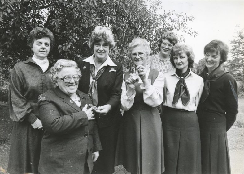 1985: Aberdeenshire Miss Alma Pawson (second left) receives a clasp from regional organiser of the WRVS Mrs Muriel Scanlon to mark her 27 years' work for the organisation. Miss Pawson (69) (second left), Flower Cottage, Braemar, received her award alongside Mrs Joe Dick (centre), 7 The Square, Tarland, who has given 25 years service. Looking on left to right are: Mrs Kathleen Marnoch, acting district organiser, Kincardine and Deeside; her secretary Mrs Anne Simpson; Mrs Mona Harcus, food organiser and Mrs Allison Gray, old peoples' welfare organiser, both Grampian Region.