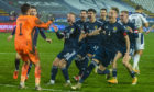 Scotland's players celebrate after David Marshall saves Aleksandar Mitrović's penalty to secure Euros qualification.