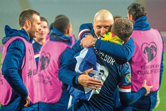 Lyndon Dykes embraces Callum McGregor after Euros qualification was secured.