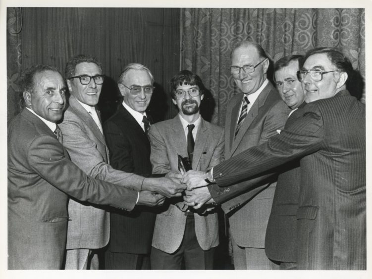 1986: Operations manager with Grampian Transport Mr Colin Smith (centre) presents the six retiring bus inspectors with their farewell gifts of wallets and notes. From left are: Inspector Charles Keenon, senior inspectors Arthur Burnett and George Tindall, chief inspector George Filby and senior inspectors John McEwen and Walter Reid.