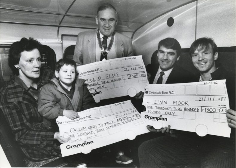 1987: Managing director of Grampian Transport Mr Moir Lockhead (second right) presents three cheques, each for £1300, from cash raised at Grampian Transport's recent 1st birthday party. Receiving them are (left to right): Mrs Linda McDougall and her son, Callum, Newtonhill, to help their Callum Wants to Walk appeal; Mr Jack Thain of Aberdeen Rotary Club, to boost the Rotarians' Polio Plus Campaign; and Alex McLeish, for the Linn Moor Appeal. The presentations took place at Grampian Transport's King Street depot.