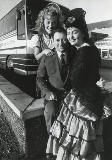 1988: Adding a continental flavour to the launch of the new holiday tours to be provided by Grampian Transport in conjunction with Tayside Transport and Mairs Coaches are Debby Gillespie and Leigh Coats with driver Mr Eddie Arthur.