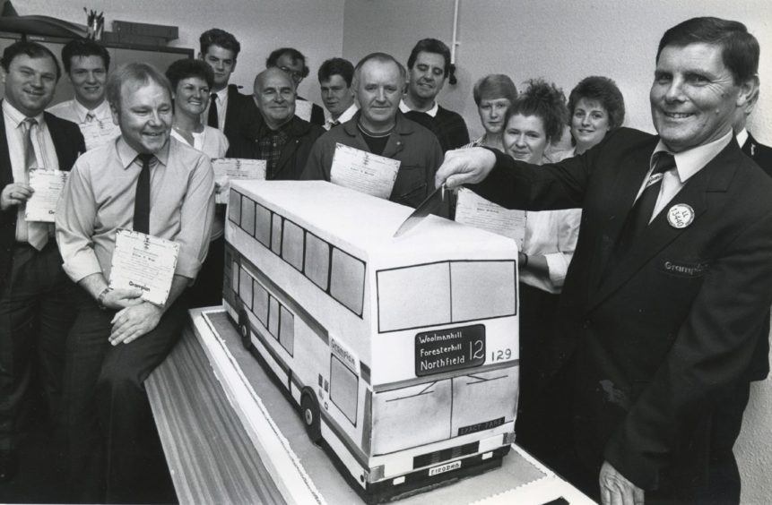 1989: Getting a slice of the cake is bus driver Mr Alexander Stuart, Summerhill, at a ceremony to mark the deal. The cake will today be given to Royal Aberdeen Children's Hospital.