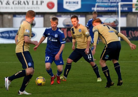Peterhead's Lyall Cameron with the ball, surrounded by Forfar players. Picture by Kenny Elrick