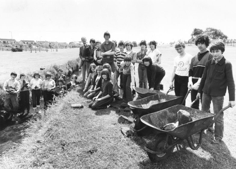 1981: Summerhill Academy 4th-year pupils are taking a break from lessons this week to carry out the first phase of a two-part community project. Through Summerfield Community Council and with the help of Aberdeen District Cleansing Department, they are tidying up the Denburn area between Fernlelea Road, Woodend and Kingsgate. Above – the pupils get stuck in to their task with history teacher James Martin and (right) smiles from Angela Manson (15) and Paula Hepburn (15) as they press on with their share of the work.