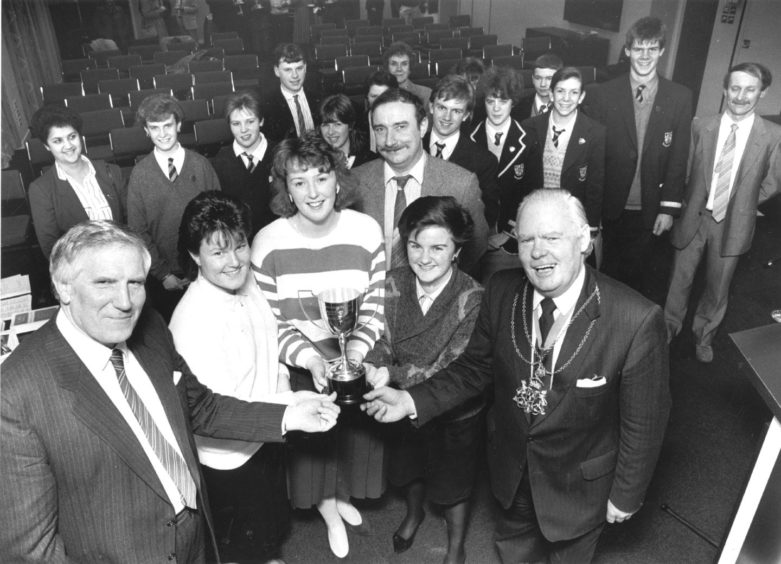 1988: Contest winners, the Summerhill Academy team of (left to right): Kim Neill, Fiona Thomson and Karen Harkin (all 16) with teacher Les Hutton (behind), are presented with the Evening Express trophy by Lord Provost Henry Rae (right) and Mr R. J. Williamson. They also received a cheque for £200, while runners-up Inverurie (back left) won £100 and third-placed Cults (back right) won £50.