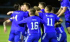 Rory McAllister is mobbed by his Cove team-mates after scoring the winner