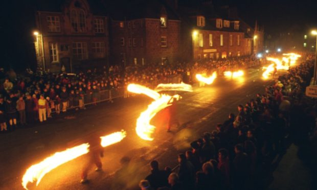 Stonehaven's Old Town High Street becomes a river of flames during the fireballs ceremony.