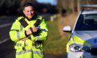 PC Phil Cameron doing speed checks with a speed gun on the A96 north of Huntly.