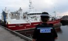 A police officer standing beside the MV Sunbeam at Fraserburgh Harbour in August 2018.