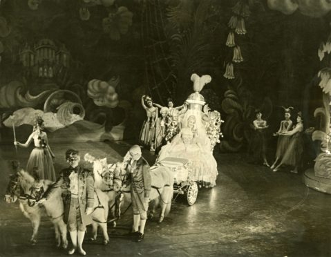 A coach and horses carry Cinderella to the pantomime ball at His Majesty's Theatre, Aberdeen in 1955.
