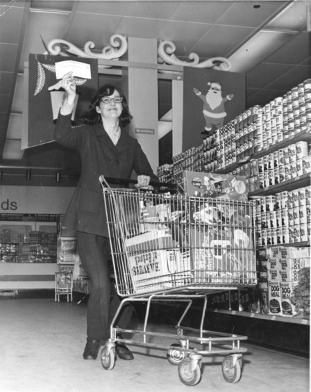 1971:  Mrs Elvira Hay, 21 Catto Crescent, Cove Bay, who won £250 in the Fix-the-Bail competition on a Green Final coupon and a shopping spree at Fine Fare supermarket, Bridge of Dee, races through the store with her haul and her £250 cheque.