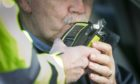 A driver using a breathalyser. Picture posed by model.