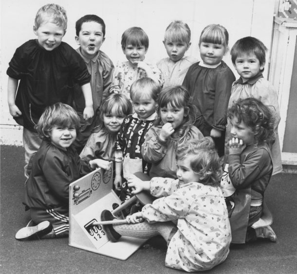 1987: Dawn Adams puts her car into gear but it looks like some of her nursery class friends are a bit doubtful about her driving skills!