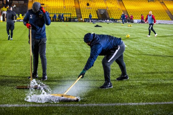 Ground staff sweep rain off the pitch during a Scottish Premiership match between Livingston and Aberdeen at the Tony Macaroni Arena.