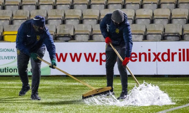 Groundstaff try to clear water off the pitch on Wednesday night.