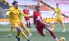 Livingston's Ciaron Brown (L) in action with Aberdeen's Ross McCrorie.