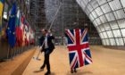 Staff members arrive to remove the United Kingdom's flag from the European Council building in Brussels on Brexit Day.