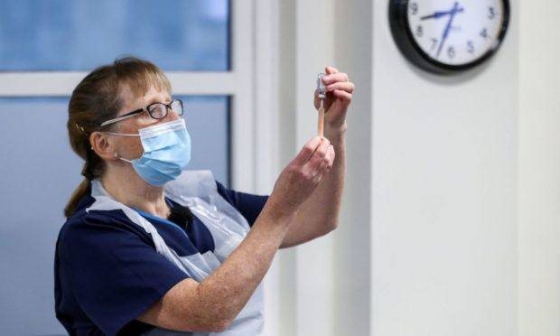 A healthcare worker holds a vial of the Oxford/AstraZeneca coronavirus vaccine.