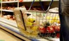Shopper with a basket full of groceries in a supermarket