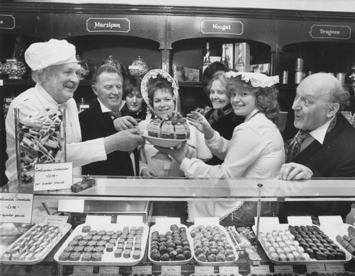 1987: The Pro-Arte Singers, who are staging Waltzes from Vienna in Aberdeen Arts Centre from April 28, decided that to get the right feel for the opening scene set in a confectionary shop/café in Vienna, they should sample some of the delights on offer in Nova, Rose Street. There, chocolate shop girl Linda Smith (centre) decided that the cast (left to right) Eric Coutts, Ian Middler, Sue Chalmers, Marjory Robb, Hilary Esson and Stewart Smith thought everything would be just a piece of cake!