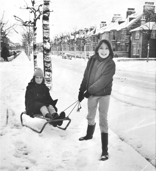 1976: Eleven-year-old Claire Darling, 70 Gladstone Place, Aberdeen, pulling her sister Caroline (12) along Forest Avenue on their sledge.