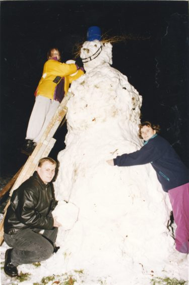1993: Putting the finishing touches to their 10ft-tall snowman last night were these members of the Stoneywood Venture Scouts. At the top of the ladder is Angela Hutcheon, while front left is Bob Wilson and on the right is Susan Cantlay. It took them one hour to create the snowman at their Waterton Road headquarters.