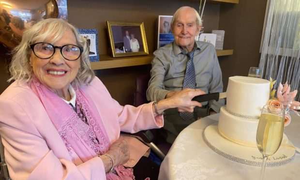 Violet and Stanley cutting their cake.