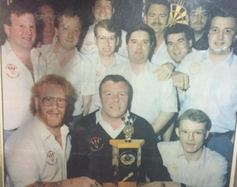 Dave Neilson with the Evening Express Trophy which he won on more than one occasion, with Bob Taylor in the middle of the back row, and Graham Hendry to his right.