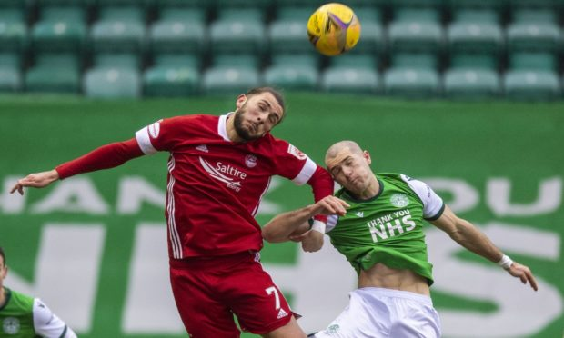 Aberdeen's Fraser Hornby (left) and Alex Gogic of Hibs battle for the ball.
