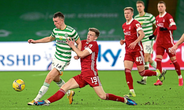 Celtic's David Turnbull (left) and Aberdeen's Lewis Ferguson battle for the ball during the Scottish Premiership match at Celtic Park, Glasgow.