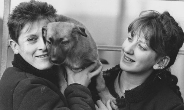 Kennel maids Julie Cockrill (left) and Marie Simpson hug Alsatian pup Peggoty at Mrs Murrays Cat and Dog Home in 1988.