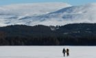 Valentina Benacchhini and (yellow Jacket) and Mattia Zenere from Italy who work locally at a hotel walk on and rest by a beautiful frozen Loch Morlich in Aviemore.