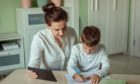 distance learning, online education at home during the covid-19 pandemic. family mom and son joyfully doing homework in the room using tablet; Shutterstock ID 1699363612; 349da3ed-023f-4314-b3d5-3478746d587f