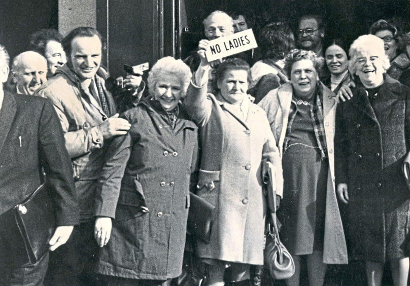 1973: Women protest in front of the Grill Bar, Aberdeen, on Union Street, trying to get access in the pub. The sign 'No Ladies' was snatched off the bar door and was passed triumphantly from one group of women to the other.