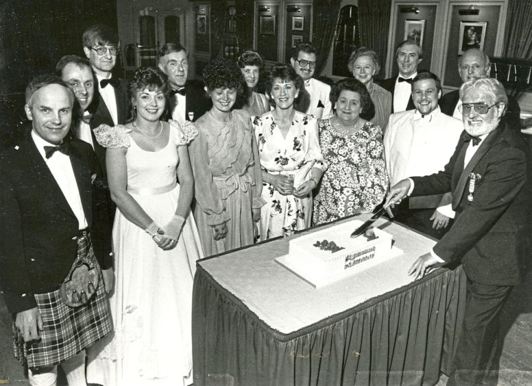 1987: The Lyric Musical Society of Aberdeen honorary president Mr George Low cuts their 35th anniversary cake in the Amatola Hotel while present and former member look on.