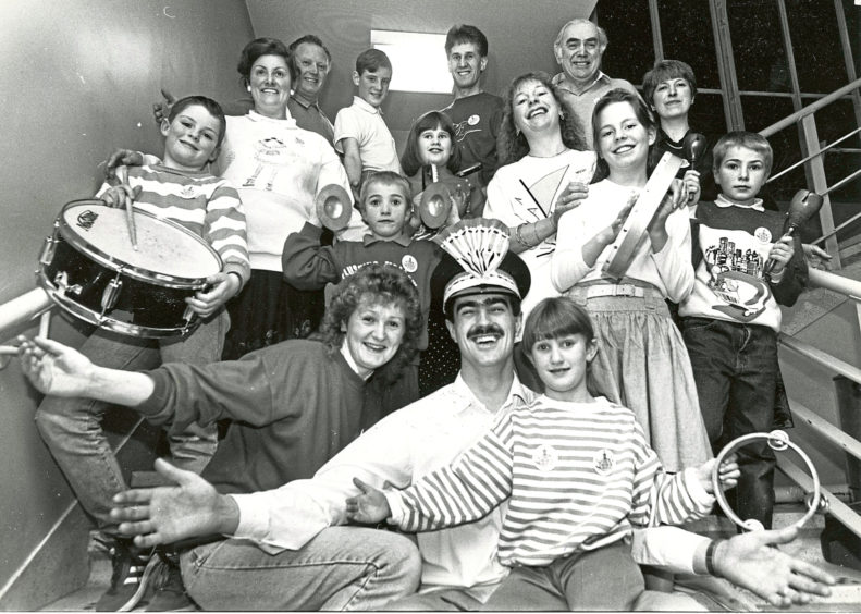 1990: Tony Burgess, who plays the lead in The Music Man to be held at His Majesty's Theatre from tomorrow until Saturday, gets into the spirit of things with his wife Pamela and seven year old daughter Lisa who are also in the show. The five other families taking part in the Lyric Music Society's latest show, gather round.