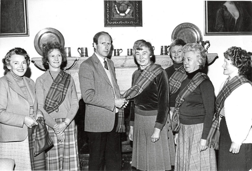 1983: A Burnett clan tartan sash is presented to Mrs Phyllis Wattie (centre), 9 Wilson Road, Banchory, by Mr J. C. A. Burnett of Leys to mark her Installation as a guide at Crathes Castle. Mrs Wattie and the other women in the picture will be helping show visitors around the castle this summer.