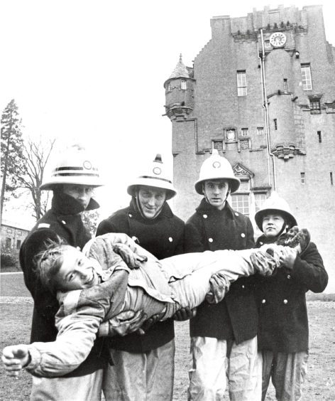 1986: Crathes lad Graham Sutherland (12), Crathes Castle Kennels Cottage, is rescued by firemen (left to right) Gordon Moir, Aberdeen, and John Morrison, Roddy Lees and Ian Hepburn, all Banchory during last nights simulated fire rescue exercise at Crathes Castle. Grampian firemen tackled a major blaze at Crathes Castle on Deeside last night. The training exercise, involving men from Aberdeen and Banchory, simulated a fire in the roof and seven casualties inside. Some were brought out down the staircase by men using breathing apparatus and others were plucked by turntable ladder from windows. A smoke generator was used to provide realism. Afterwards Sub-officer Gordon Moir, brigade training officer for retained stations, said the exercise had gone well. It was carried out very efficiently and the rescues were effected quite quickly.