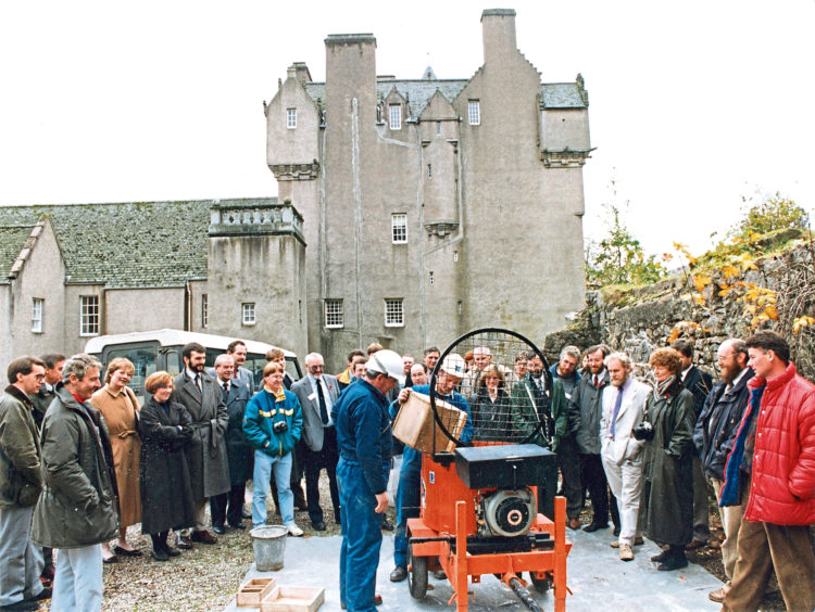 1990: Representatives concerned with the conservation of historic buildings and monuments attending a building-conservation conference held by the National Trust for Scotland, watch Mr Edward Forrest, Lumsden, and Mr Bruce Hendry, Inverness, feed special limes and mortars into a mixer at a demonstration at Crathes Castle.