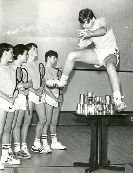 1986: All conquering Aberdeen Squash Racquets Club juniors captain Richard Irvine leaps over some of the trophies the side have won this season watched by (from left) Scott Wilson, Matthew Smith, David Irvine and Fraser Gordon. The team are looking for a sponsor to help with travelling costs.