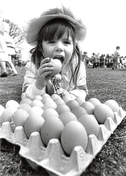 1987 - Three-year-old Melanie Gray, 172 Newburgh Circle, Bridge of Don, would rather eat her hard-boiled egg than roll it. She was taking part in a special Easter holiday Eggstra attraction for children organised by Aberdeens leisure and recreation department at Duthie Park yesterday. Sporting their best Easter bonnets, hundreds of children decorated the eggs and rolled them down the park slope. The council also laid on to inflatable play castle for the children. More than 500 eggs, donated by Homestead Eggs, were specially boiled for the occasion.