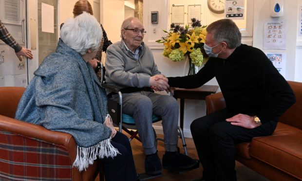Brian Forgie with his mum Moira and dad Ronnie, reunited after a year. All images were taken from outside the care home.